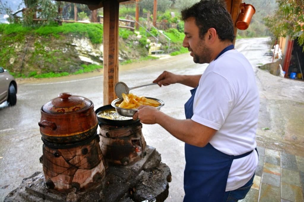 """Ο Στέλιος Τριλυράκης με τις φημισμένες πατάτες του στις φουφούδες έξω από το """"Ντουνιά""""."""